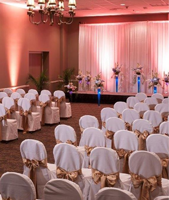 Chairs with covers and bows lined up for a weeding