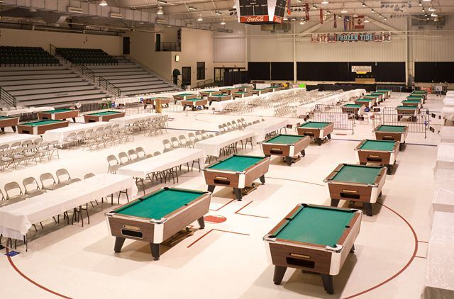 Arena set up with tables, chairs, and pool tables