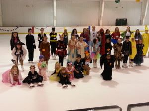 Children stand on the ice wearing costumes