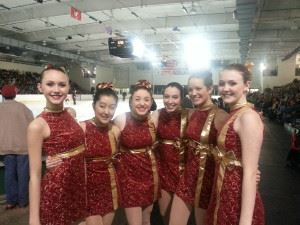 Ice skaters in costumes pose together