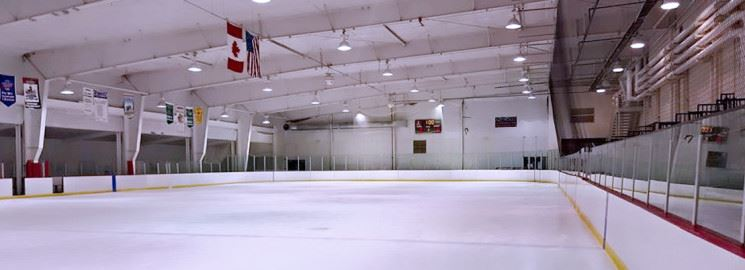 An empty ice rink with American and Canadian flags hanging from the ceiling