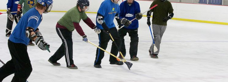 People playing broomball on an ice rink